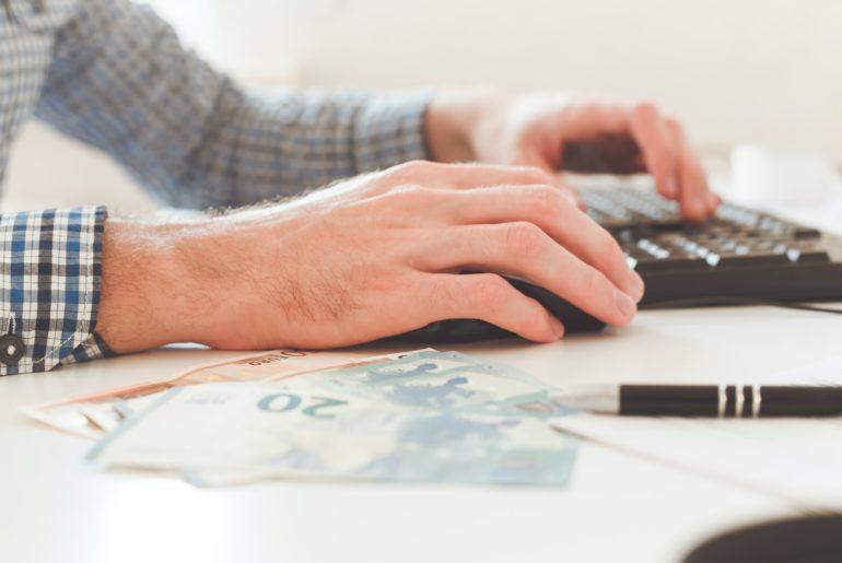 Office work. Businessman work on computer with finances. Blurred background, film effect