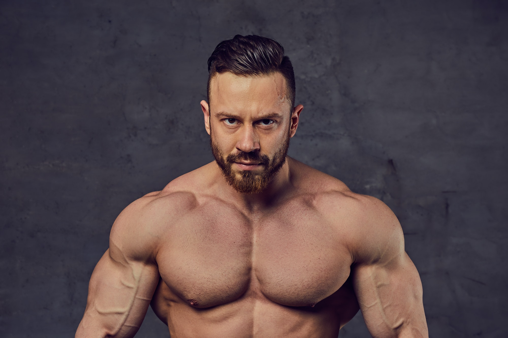 Shirtless bearded bodybuilder over grey background.